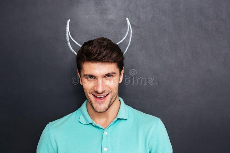 Портрет усмехаясь молодого человека с вычерченными рожками дьявола стоковые изображения rf