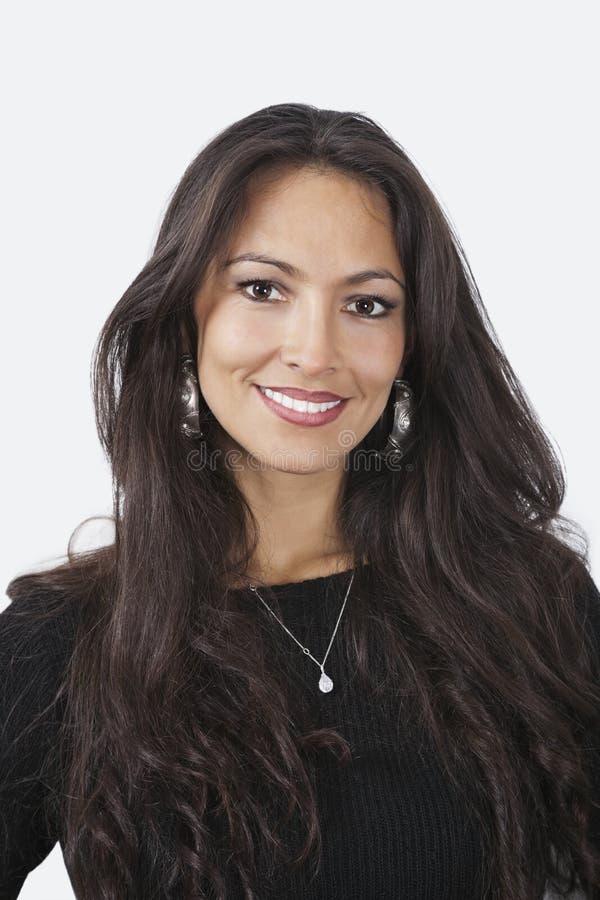 Портрет усмехаясь молодой женщины с длинними волнистыми коричневыми волосами над белой предпосылкой стоковое фото