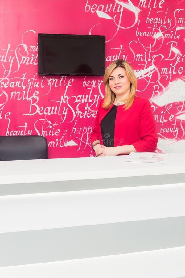 Портрет усмехаясь молодой женщины с работник службы рисепшн в офисе дантиста стоковое фото rf