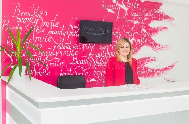 Портрет усмехаясь молодой женщины с работник службы рисепшн в офисе дантиста стоковое изображение
