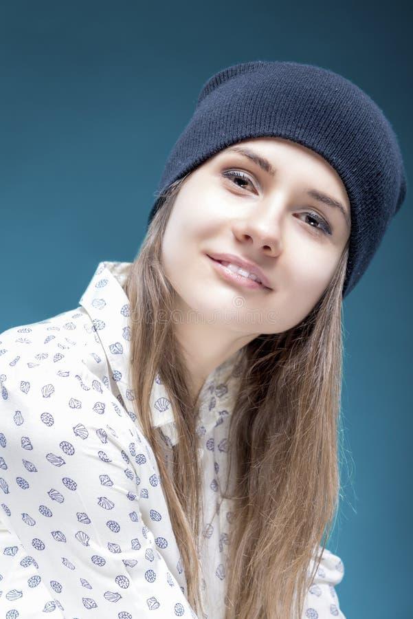 Портрет усмехаясь молодой кавказской девушки держа черную шляпу представляя против зеленой предпосылки стоковое фото