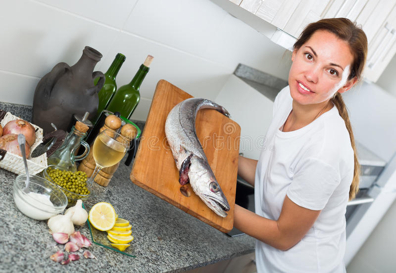 Портрет усмехаясь молодой домохозяйки с свежими мерлузами удит в руке стоковое изображение rf