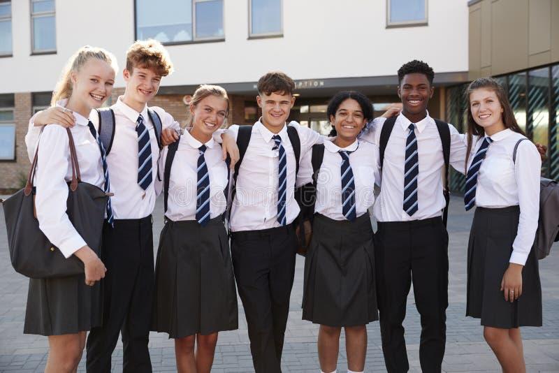 Портрет усмехаясь мужчины и женских студентов средней школы нося форму вне здания коллежа стоковое изображение