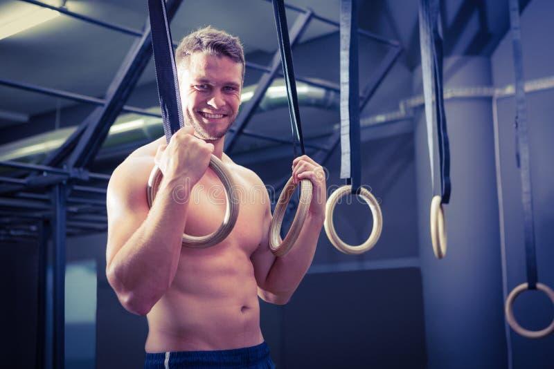 Портрет усмехаясь мышечного человека делая гимнастику кольца стоковые фотографии rf