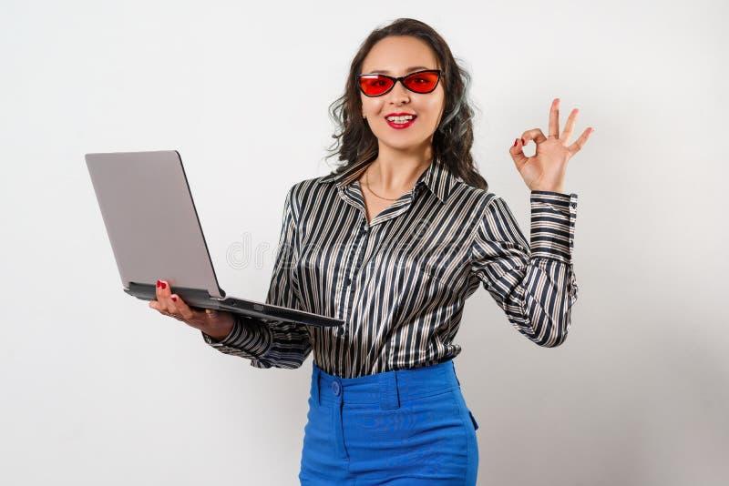 Портрет усмехаясь ноутбука и показывать удерживания коммерсантки ок на белой предпосылке стоковые фотографии rf