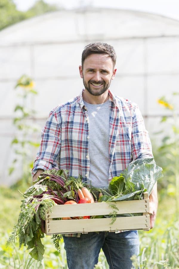 Портрет усмехаясь овощей нося фермера в клети на ферме стоковые изображения