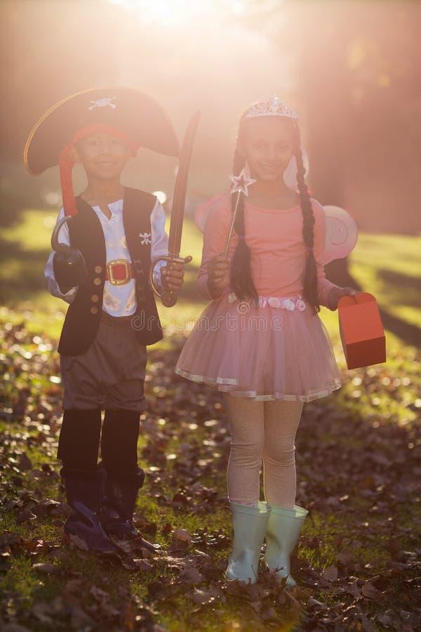 Портрет усмехаясь отпрысков нося костюмы на парке стоковое фото