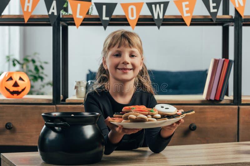 портрет усмехаясь плиты показа ребенка с печеньями хеллоуина стоковая фотография rf