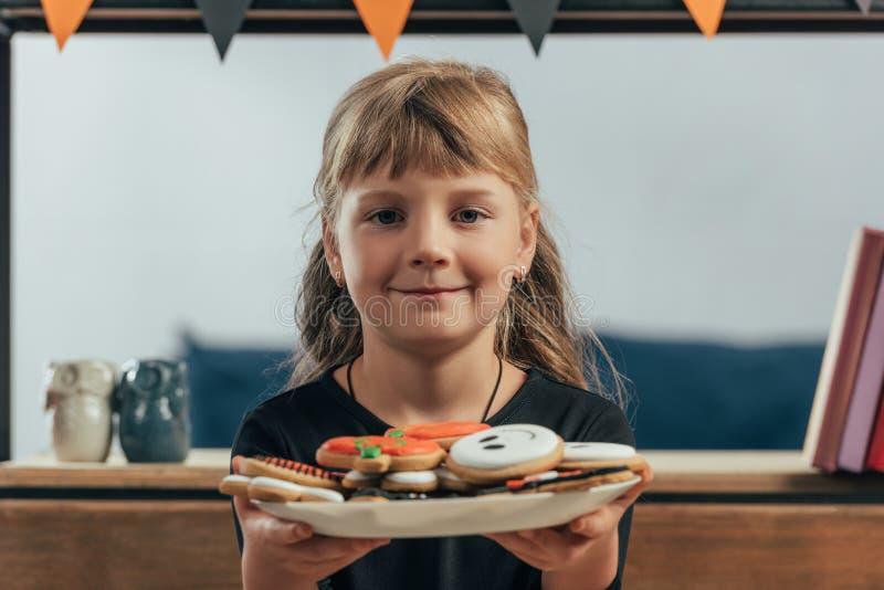 портрет усмехаясь плиты показа ребенка с печеньями хеллоуина стоковое изображение