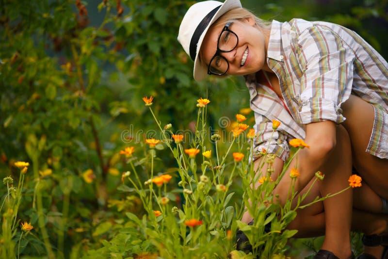 Портрет усмехаясь привлекательной женщины засаживая цветки в зеленой задворк стоковая фотография