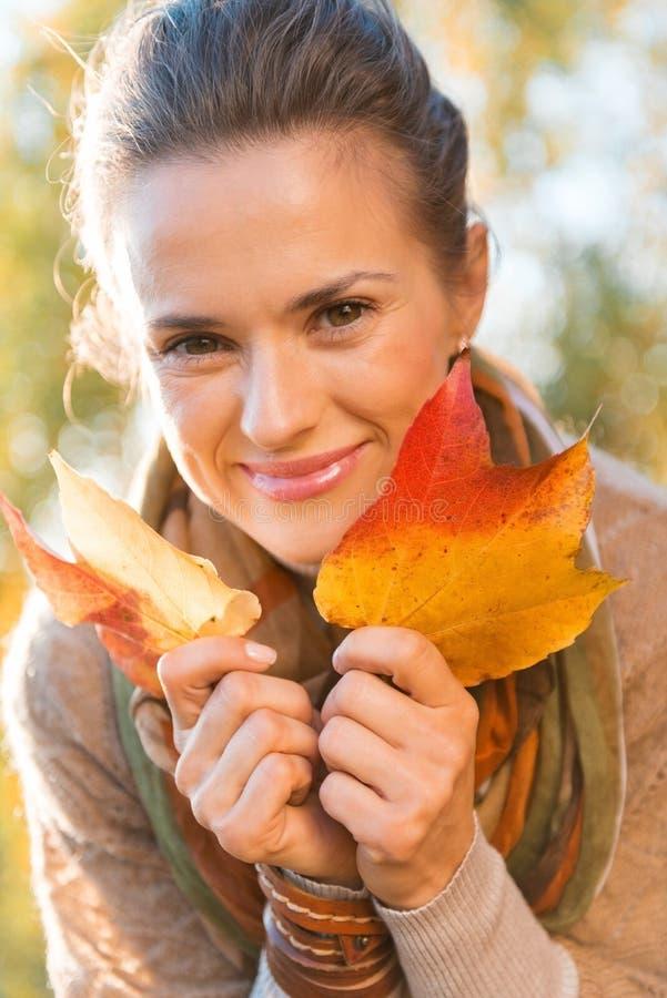 Портрет усмехаясь расслабленной женщины с осенью листает стоковые фото