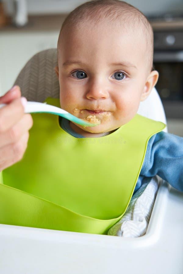 Портрет усмехаясь ребенка дома в еде Fed существования высокого стула твердой матерью с ложкой стоковые изображения rf