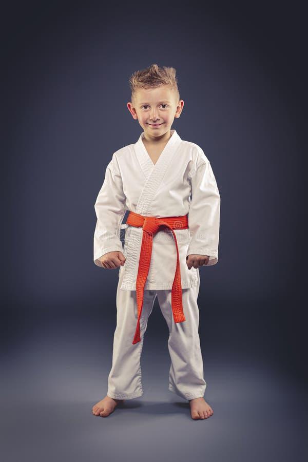 Портрет усмехаясь ребенка с боевыми искусствами кимоно практикуя стоковая фотография rf