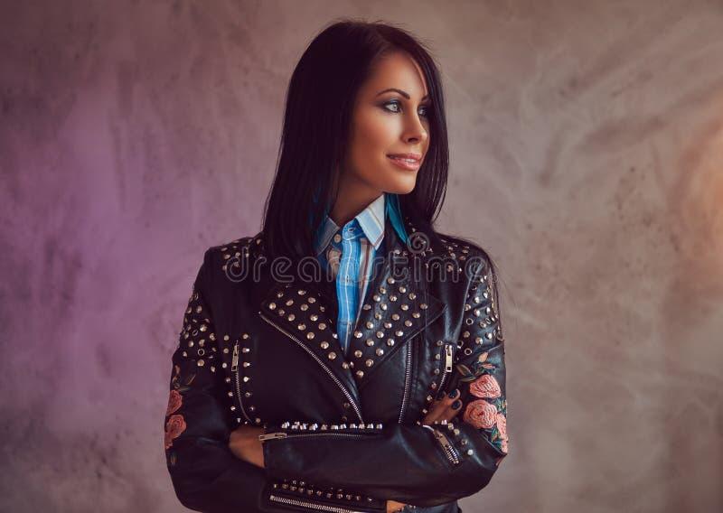 Портрет усмехаясь сексуального чувственного брюнет в стильной кожаной куртке и джинсах с пересеченными оружиями на серой предпосы стоковые изображения rf
