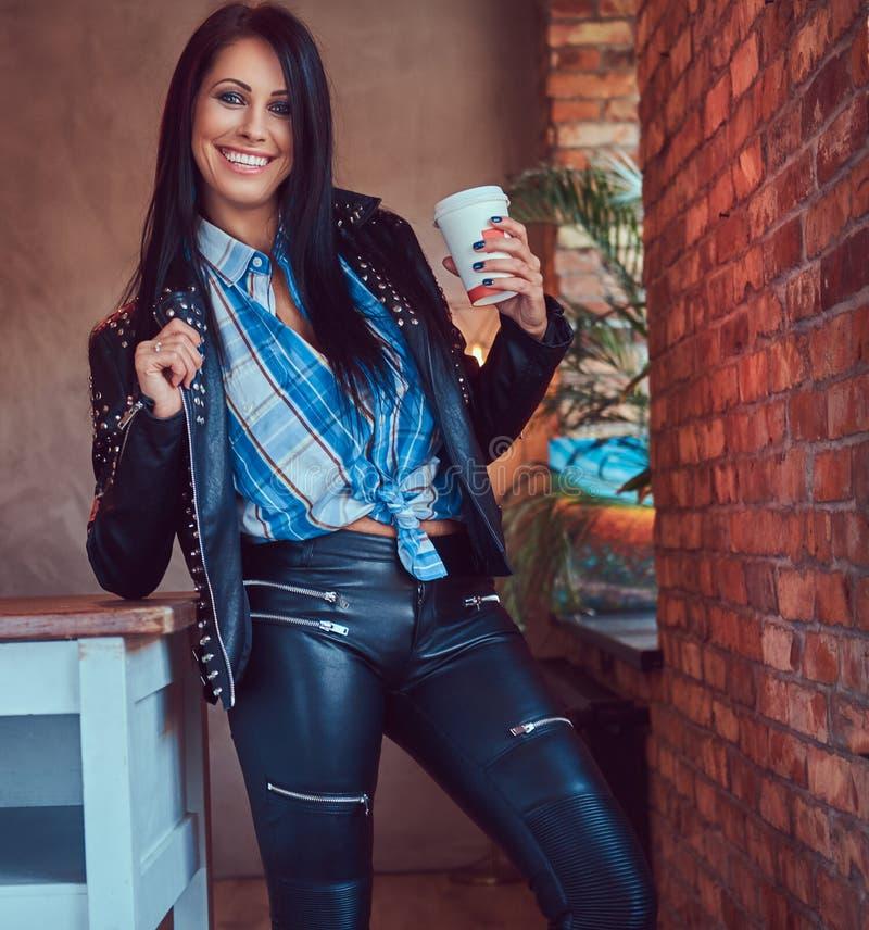 Портрет усмехаясь сексуального чувственного брюнет представляя в стильной кожаной куртке и джинсах полагаясь на таблице держит ча стоковые изображения