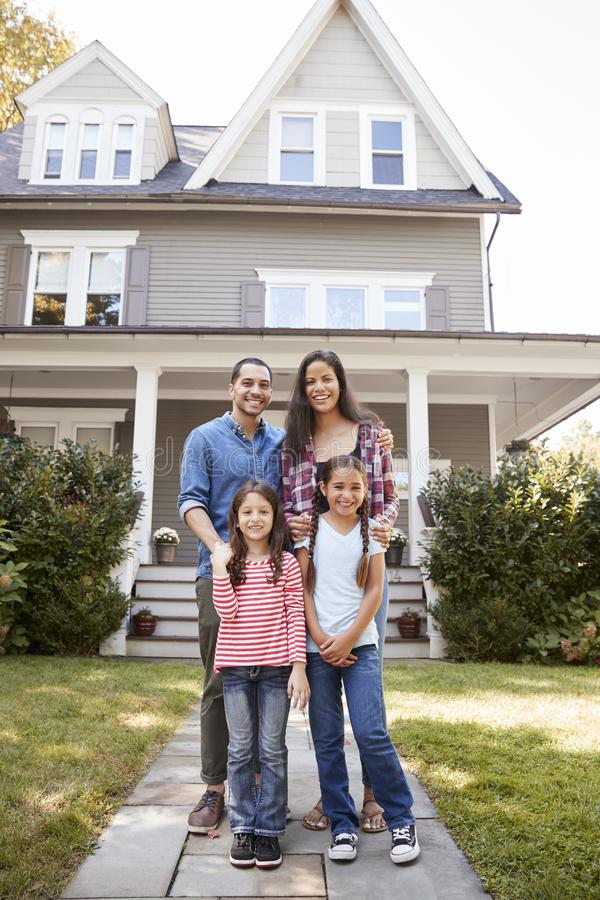 Портрет усмехаясь семьи стоя перед их домом стоковое фото rf
