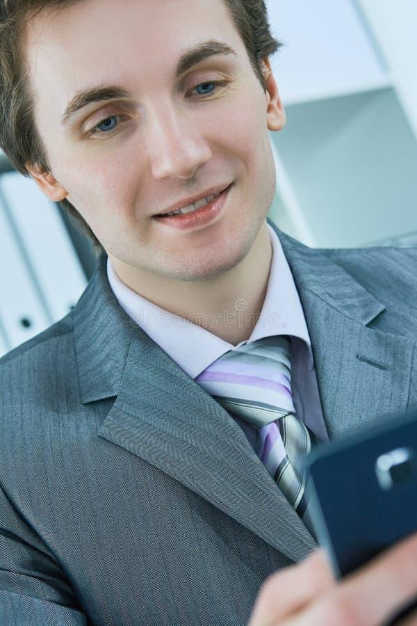 Портрет усмехаясь сообщения чтения бизнесмена с smartphone в офисе стоковое фото