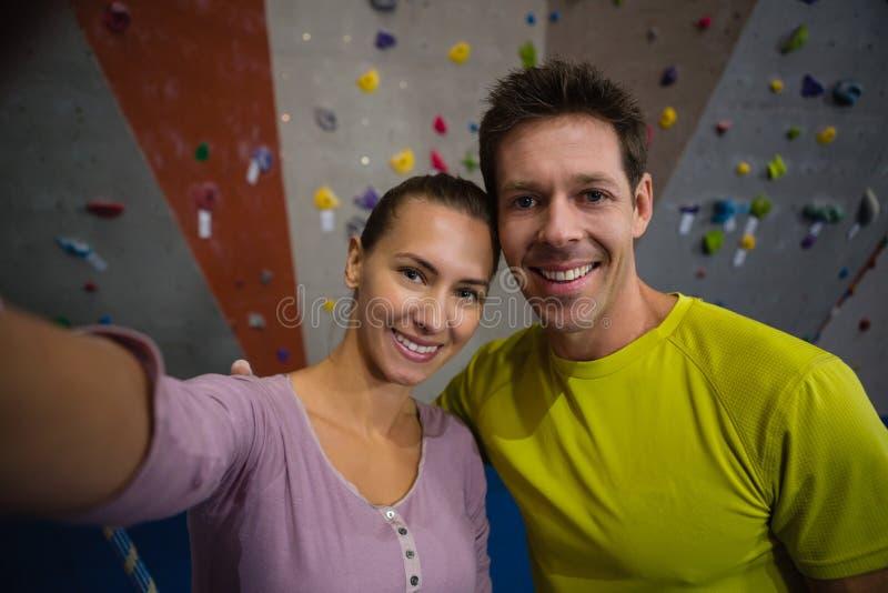 Портрет усмехаясь спортсменов готовя взбираясь стену в фитнес-клубе стоковые фотографии rf