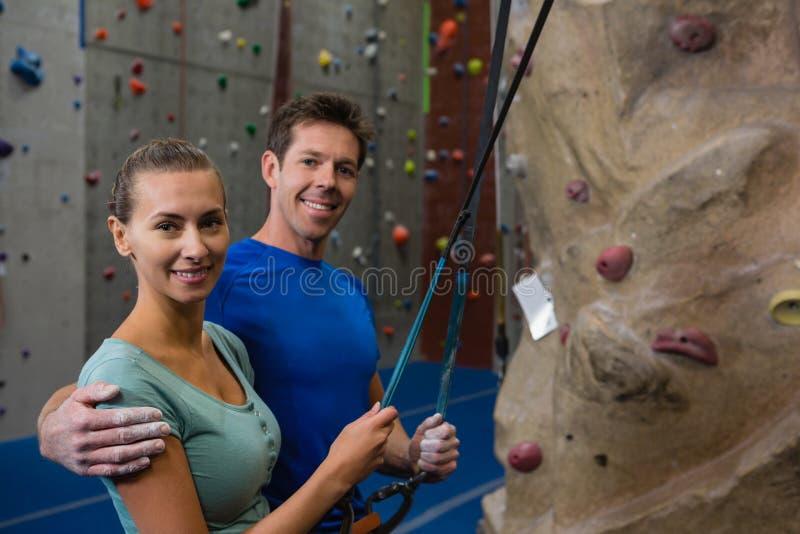 Портрет усмехаясь спортсменов держа веревочку путем взбираться стена стоковые изображения rf