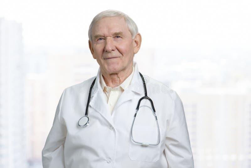 Портрет усмехаясь старого кавказского доктора в пальто лаборатории стоковое фото