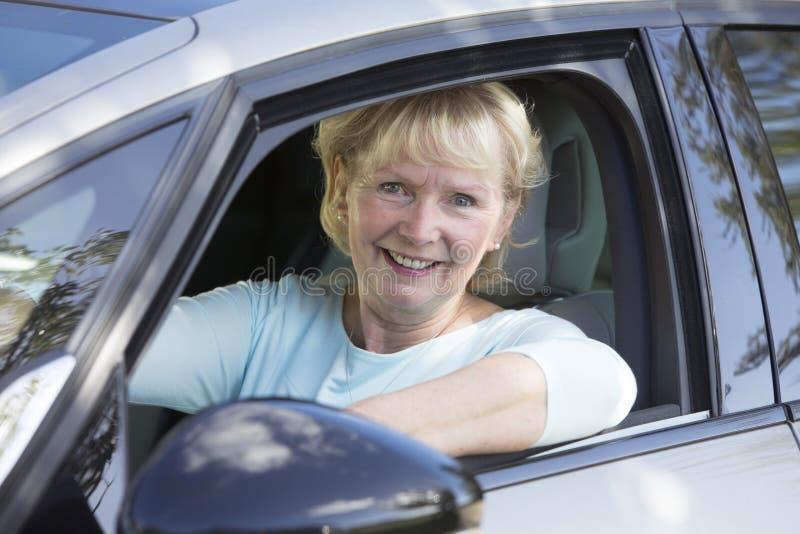 Портрет усмехаясь старшей женщины управляя автомобилем стоковое фото rf