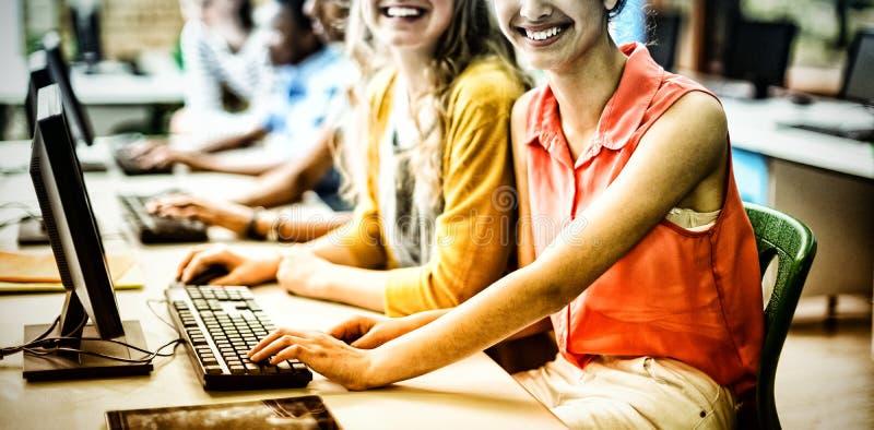 Портрет усмехаясь студентов изучая в классе компьютера стоковые изображения rf