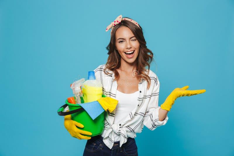 Портрет усмехаясь счастливой домохозяйки 20s нося желтое резиновое gl стоковые фото