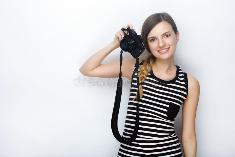 Портрет усмехаясь счастливой молодой красивой женщины в striped рубашке представляя с черной камерой фото против предпосылки студ стоковое изображение