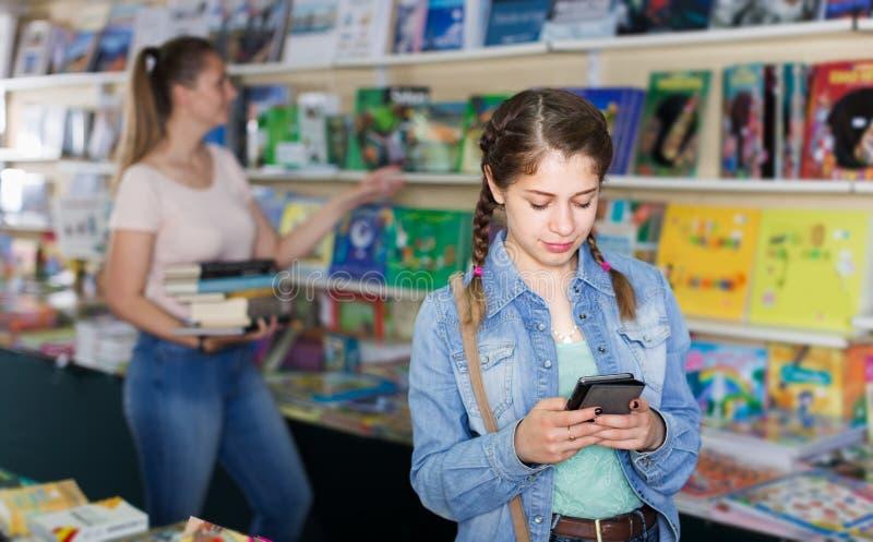 Портрет усмехаясь учебников и говорить рудоразборки девушки на teleph стоковое фото