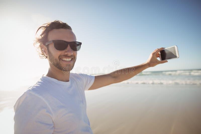 Портрет усмехаясь человека принимая selfie против ясного неба на пляже стоковое изображение rf