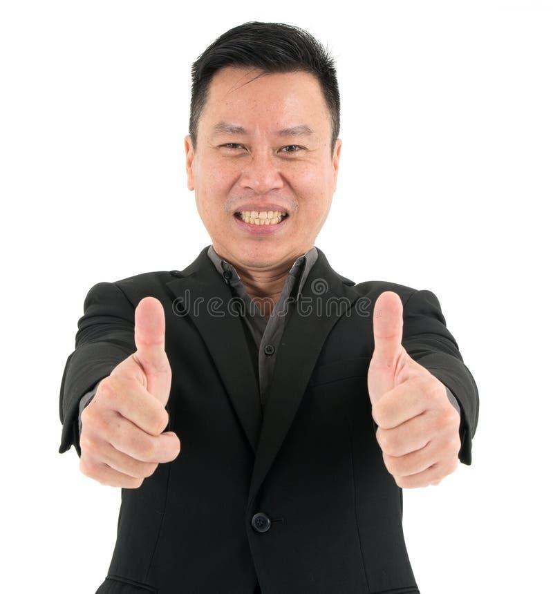 Портрет успеха уверенного бизнесмена присутствующего путем показывать 2 большого пальца руки, изолированный на белой предпосылке стоковые фотографии rf