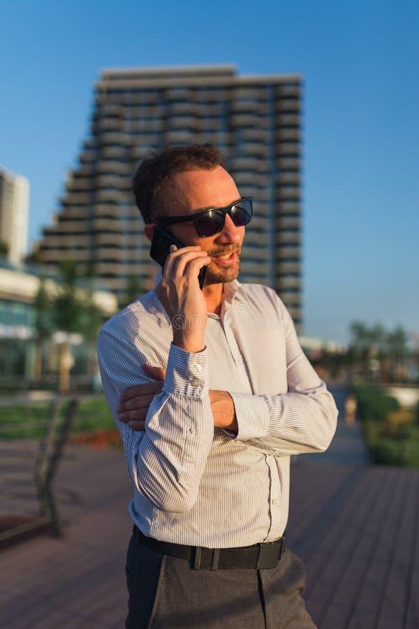 Портрет успешного бизнесмена вызывая на мобильном телефоне перед офисным зданием стоковое фото