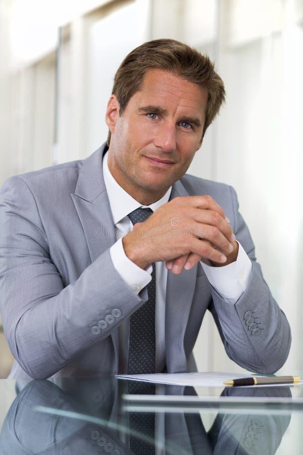 Портрет успешного бизнесмена сидя на его столе, lookin стоковые фотографии rf