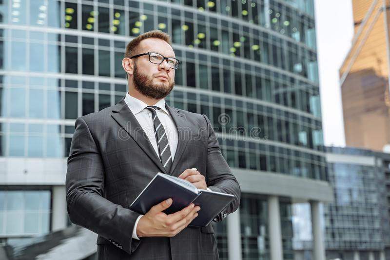Портрет успешного бизнесмена с тетрадью в его руках на предпосылке делового центра стоковое изображение rf
