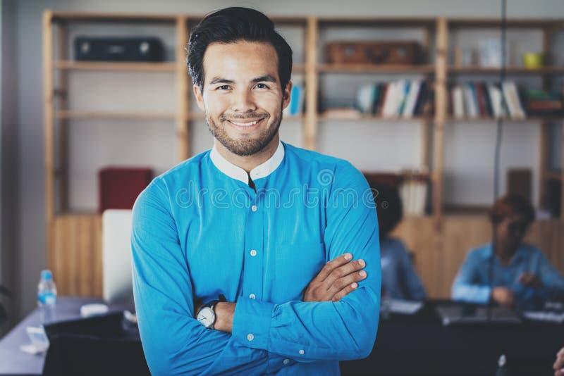 Портрет успешного уверенно испанского бизнесмена усмехаясь на камере в современном офисе Горизонтальный, запачканный стоковые изображения rf