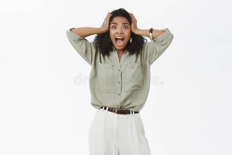 Портрет устрашенный оглушенная и сотрясенная Афро-американская женщина видя ужасающую сцену кричащую от страха стоковое фото