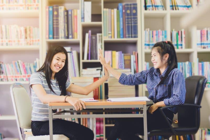 Портрет ухищренных азиатских чтения студента и исследования делать стоковые изображения rf