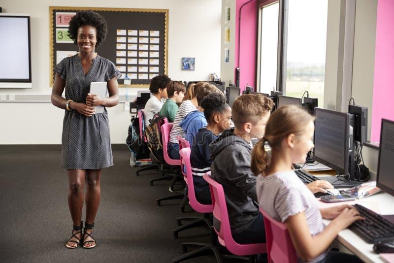 Портрет учительницы держа линию преподавательства планшета цифров студентов средней школы сидя экранами в классе компьютера стоковое фото rf