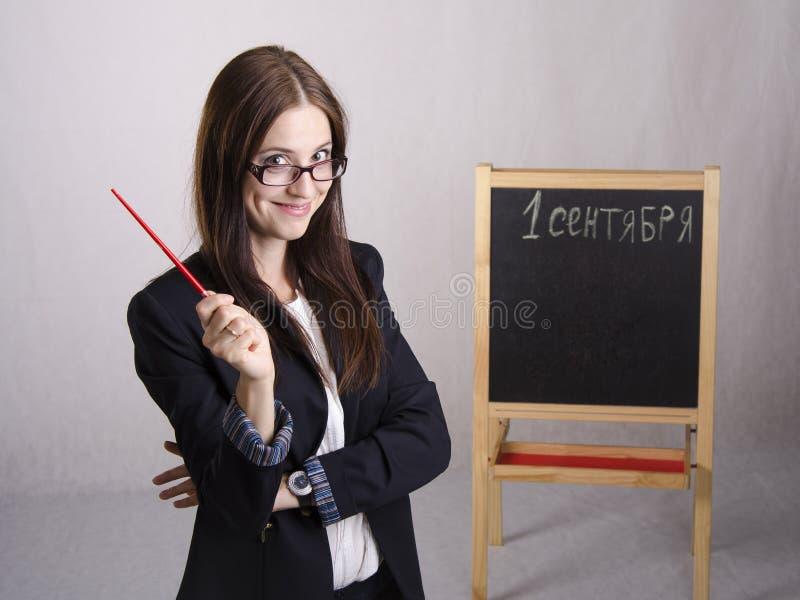 Портрет учителя, с указателем и доской на заднем плане стоковое фото