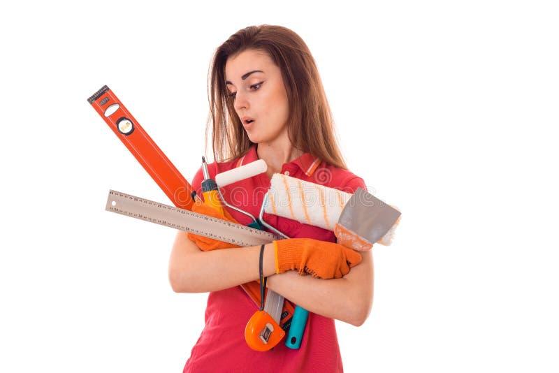 Портрет удивленной детенышами женщины здания брюнет в красной форме с инструментами в руках делает реновацию изолированных дальше стоковое изображение