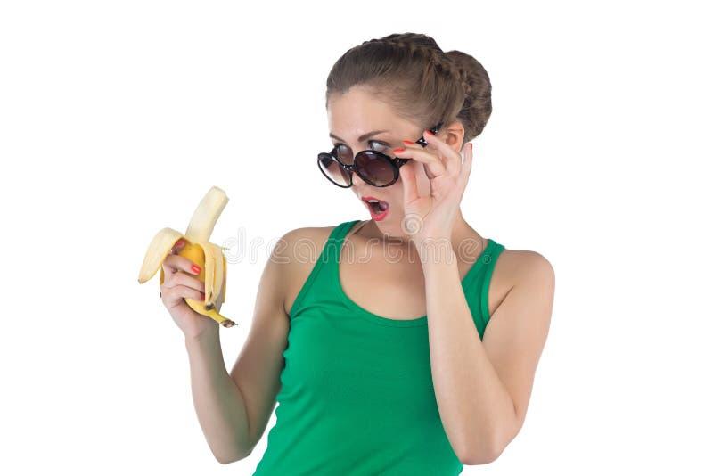 Портрет удивленной женщины с бананом и солнечными очками стоковое фото rf