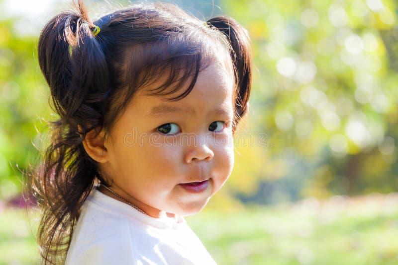 Портрет улыбки и смотреть маленькой девочки камеру стоковое изображение rf