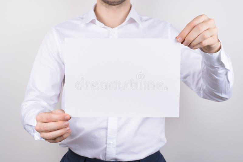 Портрет фото крупного плана красивого серьезного парня держа белую ясную чистую бумажную доску в copyspace предпосылки рук сером стоковые изображения