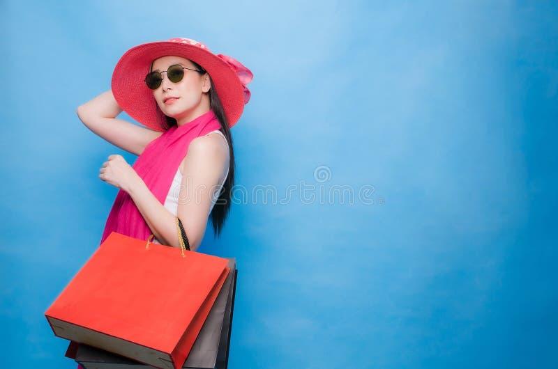 Портрет футболки белизны платья возбужденной красивой девушки нося, розовой шляпы и солнечных очков держа хозяйственные сумки изо стоковое фото rf