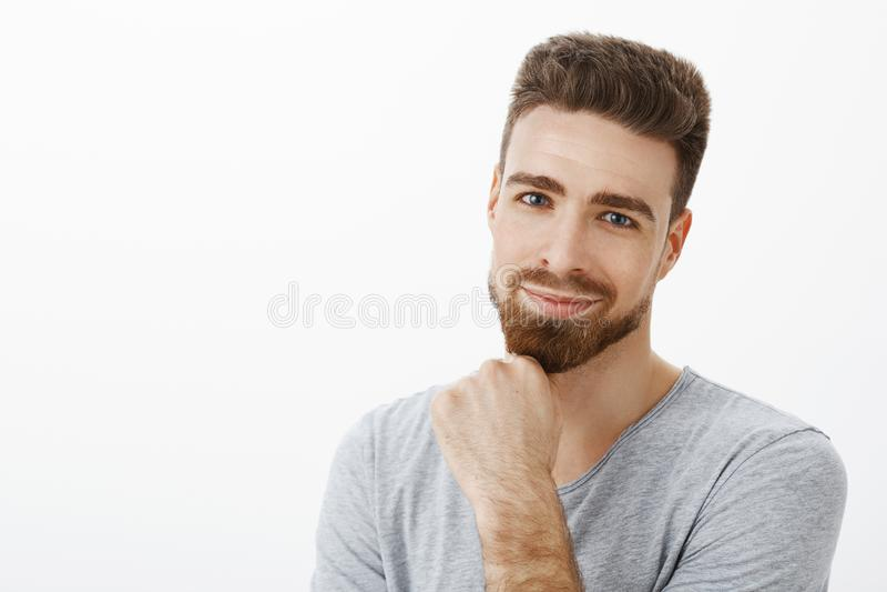 Портрет харизматического и умелого очаровательного умного человека с бородой и коричневым подбородком и ухмыляться затирания стил стоковая фотография rf