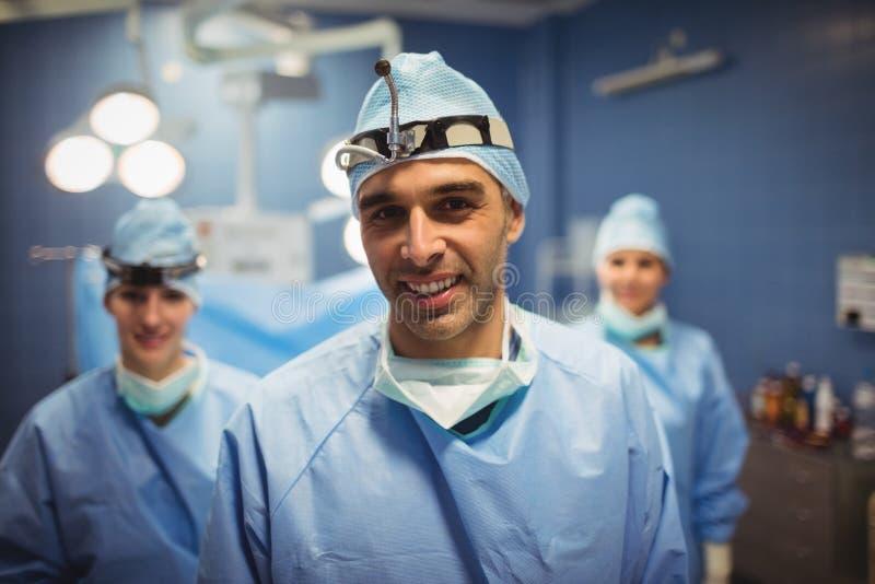 Портрет хирурга и медсестер стоя в комнате деятельности стоковые фото