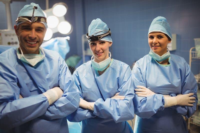 Портрет хирурга и медсестер стоя с оружиями пересек в комнату деятельности стоковое изображение