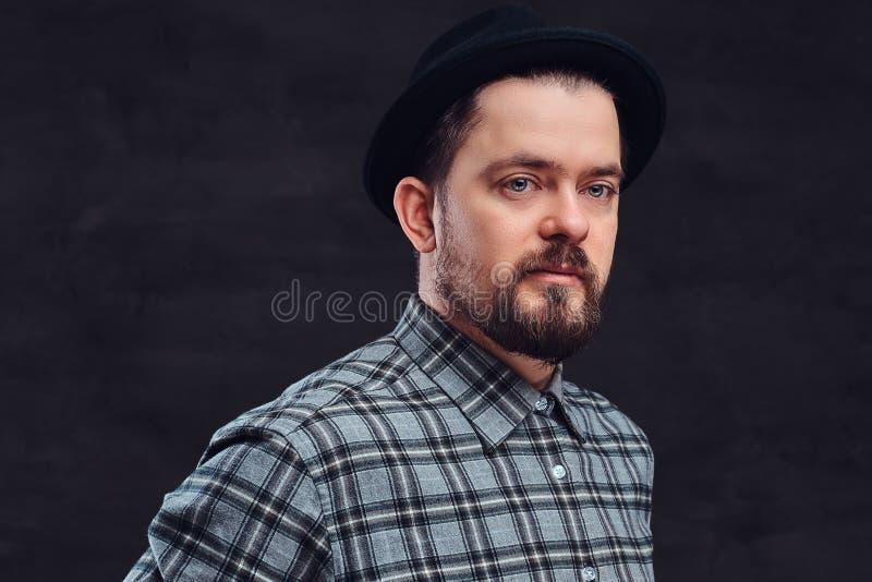 Портрет человека битника среднего возраста с бородой и стилем причёсок одел в checkered рубашке и шляпе, представлении в студию стоковые фото