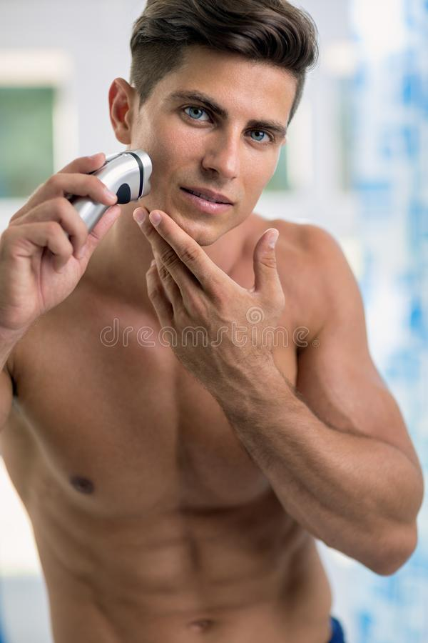Портрет человека брея подбородок и щеку электрическим шевером стоковое фото rf