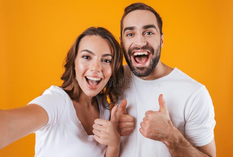 Портрет человека и женщины 2 европейского людей усмехаясь пока принимающ фото selfie, изолированный над желтой предпосылкой стоковое фото